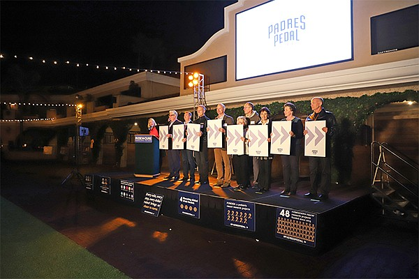 Padres Pedal the Cause Executive Director Anne Marbarger, left at podium, is joined by the beneficiaries who will receive more than $2.9 million in funding for cancer research: Steve Jennings, left, Reuben Shaw, Greg Daniels, James Short, Suzy and Jamie Simon, Barbara Parker, Kristiina Vuori and Donald Kearns. Photo courtesy of Padres Pedal the Cause