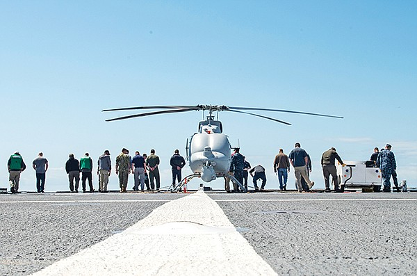Sailors and Northrop Grumman employees walk the flight deck of the USS Montgomery looking for debris during the first test of the MQ-8C Fire Scout in March 2018. The Montgomery is a Littoral Combat Ship based in San Diego. Photo by Mass Communication Specialist 3rd Class Zachary Eshleman, courtesy of U.S. Navy