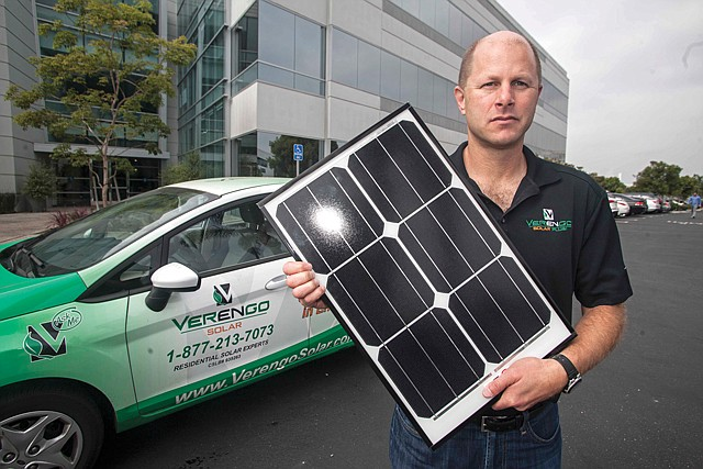 Out of Game: Verengo exec. Ken Button holds solar panel in 2013.