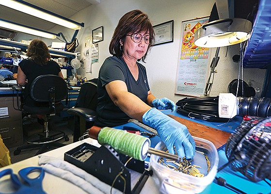 Mildred Fernandez solders pins to connectors at her station in the RF Industries plant off Miramar Road in June. RF Industries is acquiring C Enterprises LP of Vista. File photo by Jamie Scott Lytle