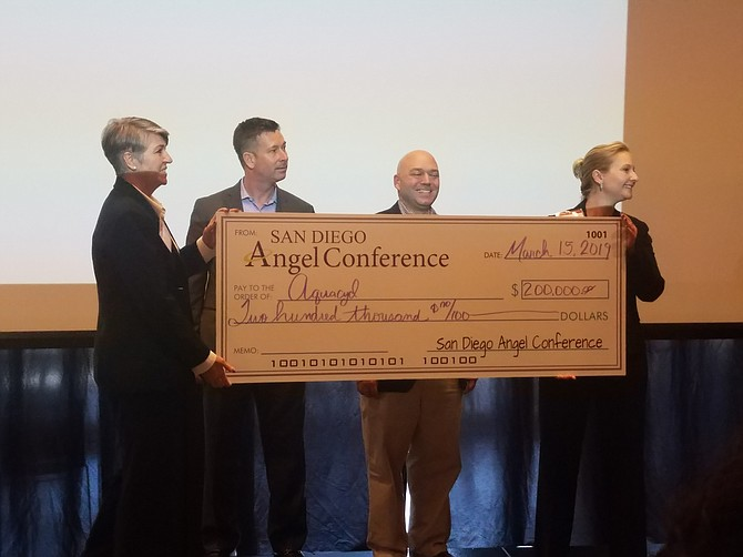 Mysty Rusk (left), director of the Brink Small Business Development Center at the University of San Diego, presents the winning check to AquaCycl CEO Orianna Bretschger (right).