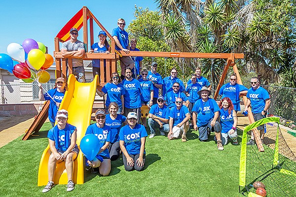A group of volunteers from Cox Communications and Cox Charities celebrate a backyard makeover for the Make-A-Wish Foundation as part of its giving program. Photo courtesy of Cox Communications