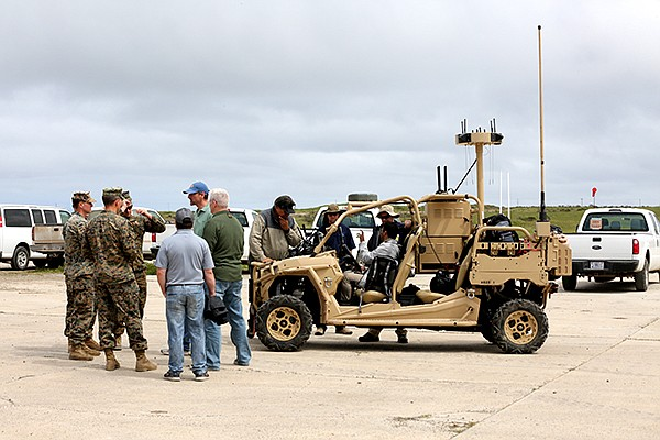 Military members and contractors confer near a vehicle loaded down with electronics on San Clemente Island April 3 during the ANTX West war games. Photo by Alan Antczak, courtesy of U.S. Navy