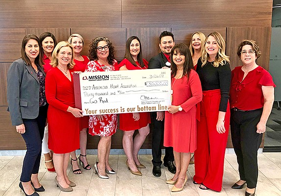 Teresa Contreras, VP Development for the American Heart Association, far left, accepts a check from Go Red for Women team at Mission Federal: Angie Lasagna, left, Debra Schwartz, Heather Schmidt, Brenda Grahm, Shannon Doane, Davee Schulte, Sherry Special, Chelsy Clark, Gloria Watson and Paula Morgan. Photo courtesy of Mission Federal Credit Union