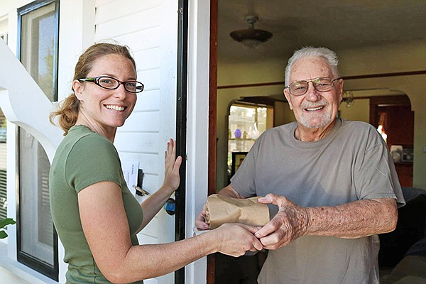 A volunteer for the Hand Up Food Pantry and FoodMobile program delivers food to a senior. Photo courtesy of Jewish Family Service of San Diego