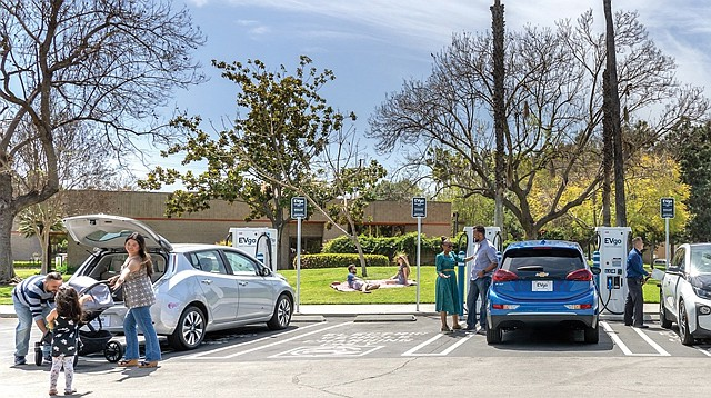 """Multi-tasking: Drivers plug into an EVgo """"fast charging station"""" in Anaheim."""