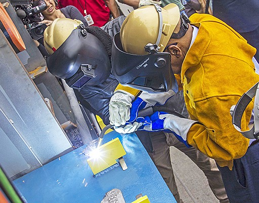 Rep. John Lewis of Georgia, right, welds his initials into a plate that will become part of the hull of the USNS John Lewis during ceremonies May 13 at General Dynamics NASSCO in Barrio Logan. Photo courtesy of General Dynamics NASSCO