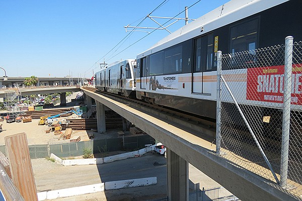 Light rail cars maneuver over LA Metro's recently built route south of downtown Los Angeles. Cubic Corp. supports the fare payment system for the Los Angeles transit agency. Photo courtesy of LA Metro