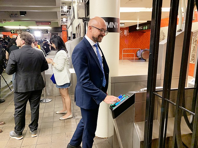 Cubic Corp. executive Matt Cole taps his phone to ride the New York City subway on the day new fare collection technology went into service. Photo courtesy of Cubic Corp.