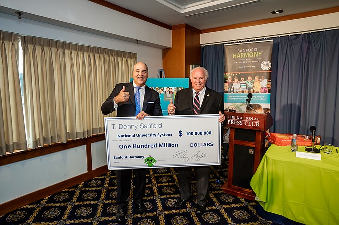 A $100 million check presented by philanthropist Denny Sanford, right, to National University Chancellor Michael Cunningham features a central character in the Sanford Harmony curriculum. The green extraterrestrial is Z, who is neither a he or she — just a Z. Photos courtesy of National University System.
