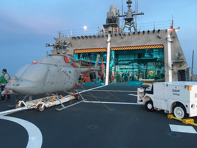 A U.S. Navy MQ-8C Fire Scout, missing its four rotor blades, in the environment where it will work — on the deck of a Littoral Combat Ship, outside its hangar. This view is from 2017. The unmanned helicopter is on the USS Montgomery in the Pacific Ocean. Photo courtesy of U.S. Navy.