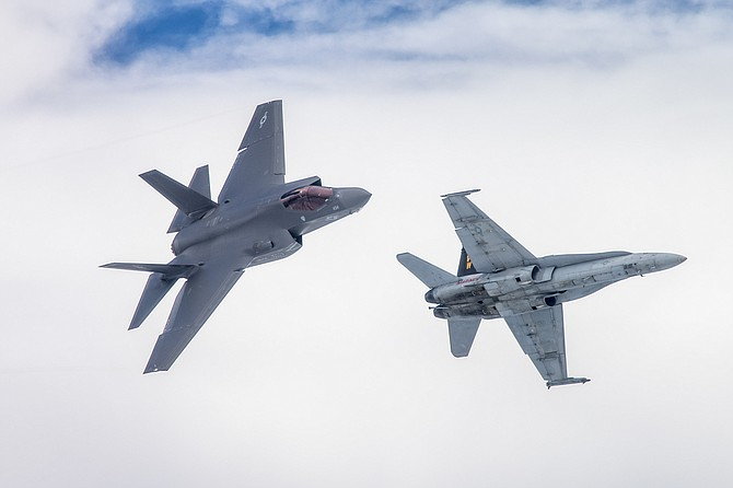 A U.S. Marine Corps F-35, left, flies with its predecessor, an F/A-18. Photo by Lt. Cmdr. Darin Russell courtesy of U.S. Navy.