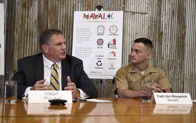 James Geurts, left, and U.S. Marine Corps Capt. Jon Margolick discuss the formation of Tech Bridges in Arlington, Virginia. Photo courtesy of U.S. Navy.