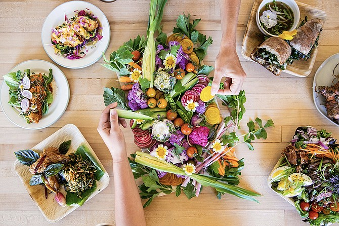 The menu at Enclave Adventurous Superfood LLC includes a crudites board with raw garlic spread, hemp seeds and microgreens. Photo courtesy of Enclave Adventurous Superfood LLC.