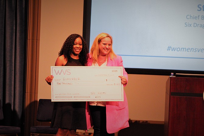 Local angel investor and Women's Venture Summit founder Silvia Mah hands the check to EnrichHer CEO Roshawnna Novellus. Photo by Elise Reuter.