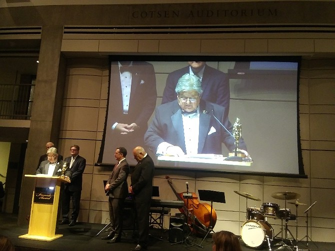 Mike Quiroga at podium and on screen accepts Fernando Award at Skirball Cultural Center.