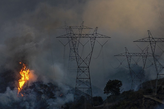 Flames heat up high power lines at the Saddleridge Fire on Oct. 11, 2019. The fire has spread to more than 8,000 acres and burned at least two dozen homes
