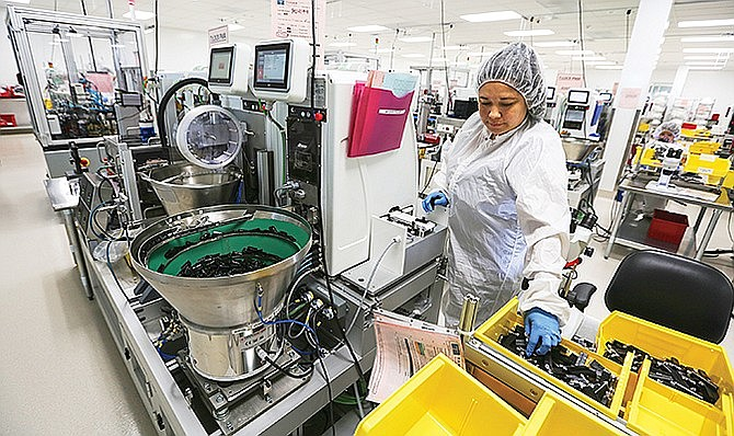 Brenda Infante loads cartridges into an automation system at the Tandem Diabetes Care manufacturing plant in San Diego. Photo by Jamie Scott Lytle.