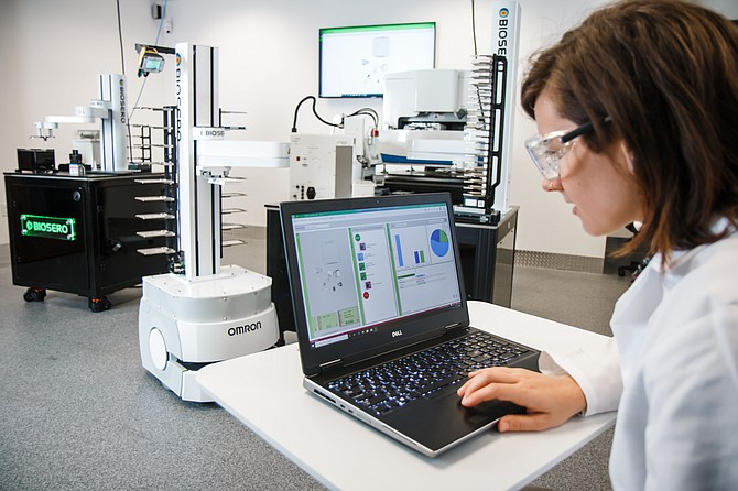 Amelia Wilson, a design engineer at Biosero, looks at a laptop in the company's mock lab. The company recently opened the lab to demonstrate how it links various automation devices. Photo courtesy of Biosero Inc.