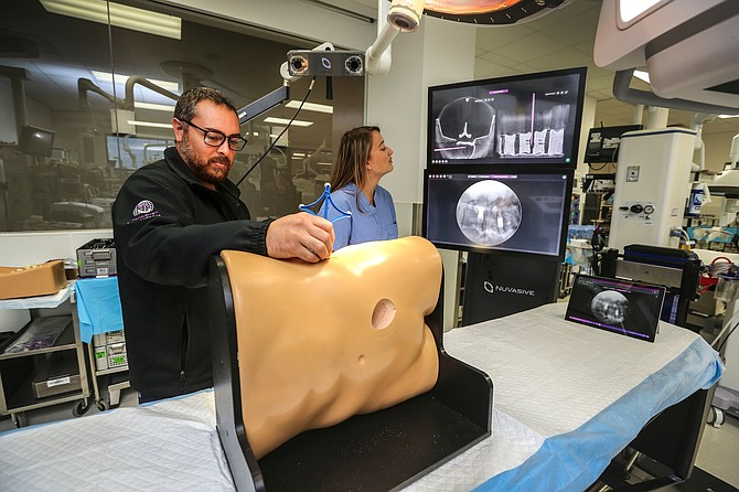 NuVasive employee Chris Wing, left, and Jenna Colburn demonstrate technology that trains surgeons in lateral spine surgery at NuVasive's headquarters. Surgeons come to its campus from around the world to learn the technique. Photo by Jamie Scott Lytle.