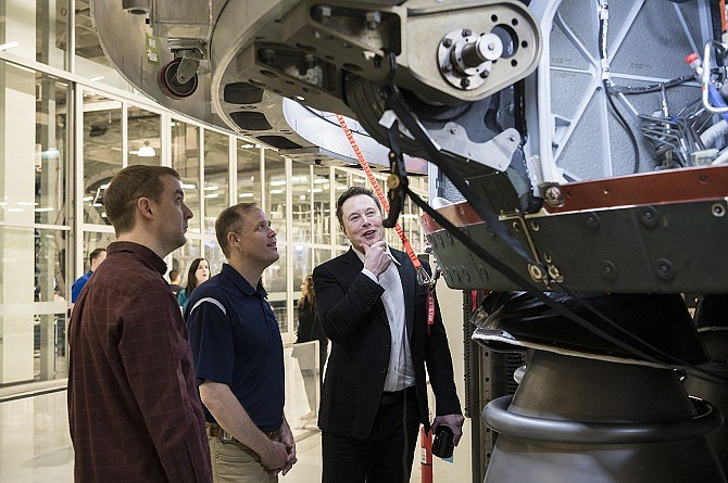 SpaceX Chief Engineer Elon Musk, right, speaks to NASA Administrator Jim Bridenstine, center, and SpaceX Vice President of Propulsion Engineering, Will Heltsley, left, while viewing the OctaWeb, part of the Merlin engine used for the Falcon rockets, at the SpaceX Headquarters, Thursday, Oct. 10, 2019 in Hawthorne, CA. Photo credit: (NASA/Aubrey Gemignani)