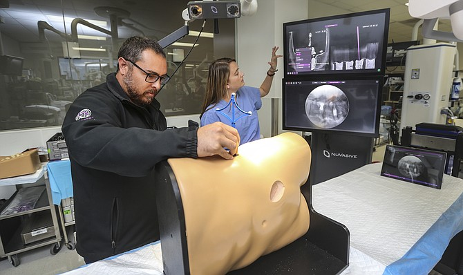 NuVasive employee Chris Wing, left, and Jenna Colburn demonstrate technology that trains surgeons in lateral spine surgery at NuVasive's headquarters. The elimination of a 2.3% excise tax on medical devices benefits companies like NuVasive. Photo by Jamie Scott Lytle.
