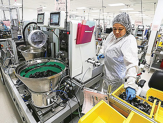 Brenda Infante loads cartridges into an automation system at the Tandem Diabetes Care manufacturing plant. Photo by Jamie Scott Lytle.
