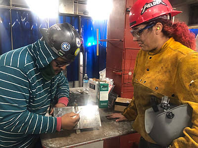 Welding instructor Carlos Garcia reviews a point with student Brittany Bynum. Photo courtesy of General Dynamics NASSCO.