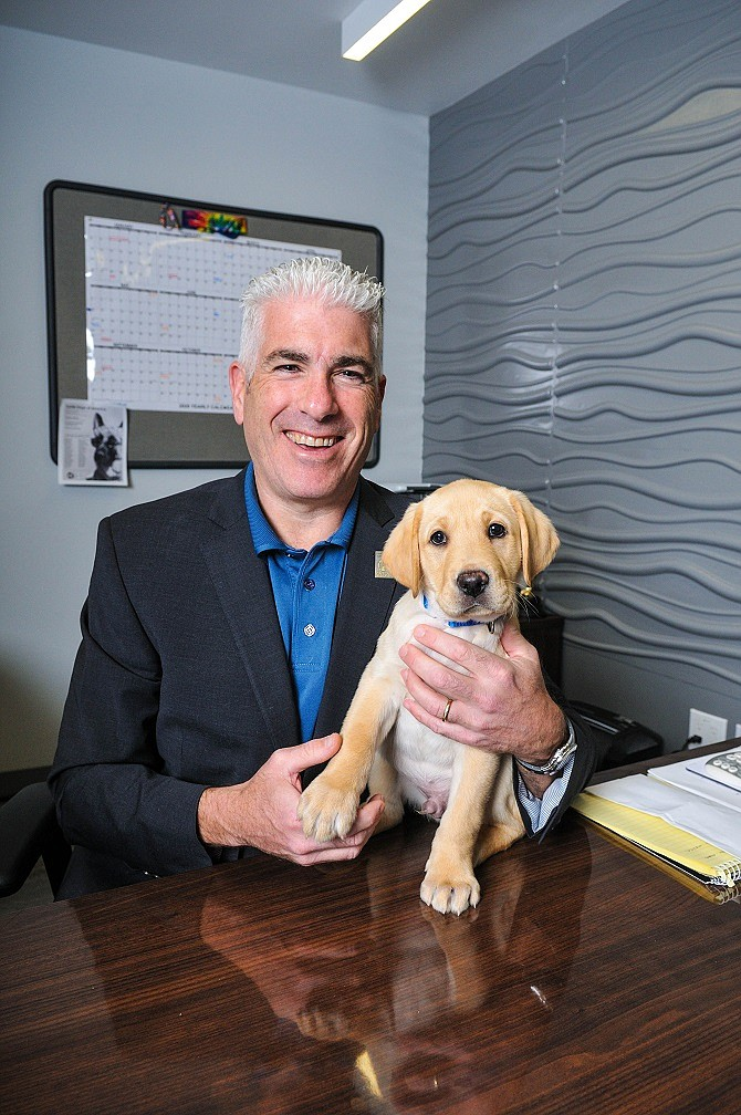 Russell Gittlen, President and Director, Guide Dogs of America with a puppy in training.