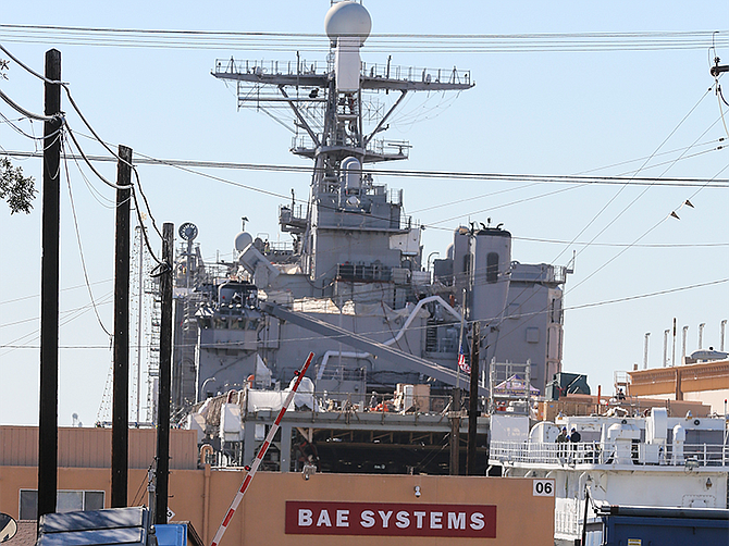 A U.S. Navy warship looms above the entrance to BAE Systems San Diego Ship Repair.