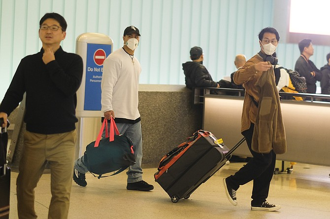 Travelers wearing masks arrive at LAX.