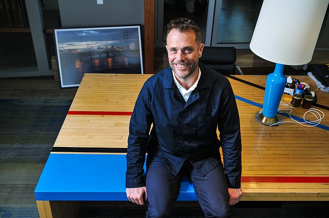 Matt Jarvis, co-chairman, 72andSunny advertising agency, sitting on his desk made from Pauley Pavilion basketball court.