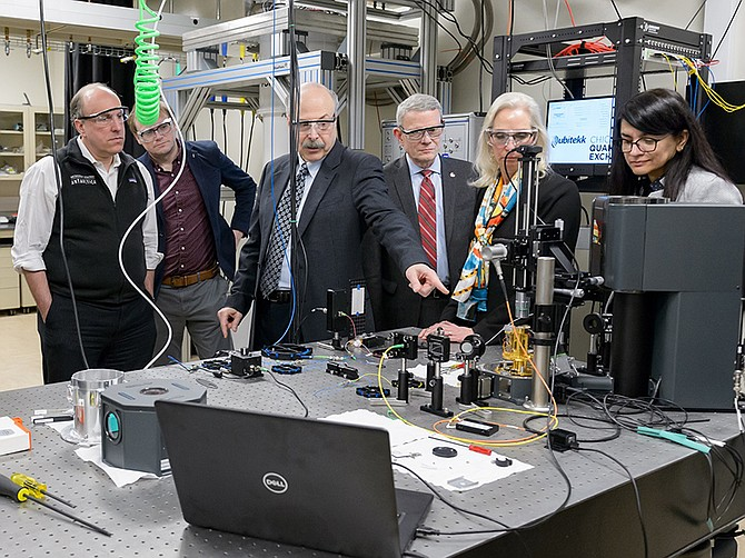 Photo courtesy of Argonne National Laboratory. Officials discuss an experiment that sent entangled photons though a 52-mile long fiber optic network near Chicago in February.