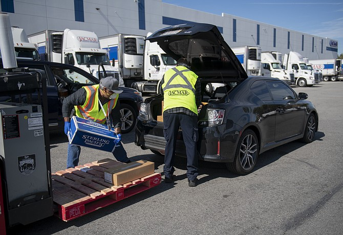 Workers load groceries into a car at Jacmar's warehouse in the City of Industry.