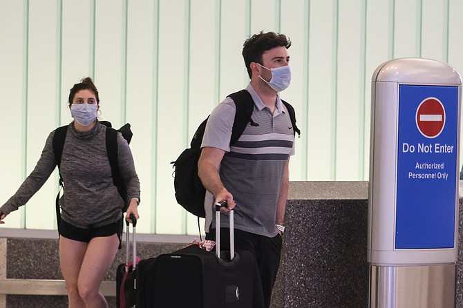 """Travelers wearing masks arrive at LAX. LAX is """"cautiously optimistic"""" about summer travel."""
