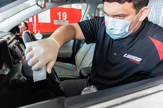 Longo Toyota Service Valet Jayden Hernandez follows safety protocols to clean vehicles.