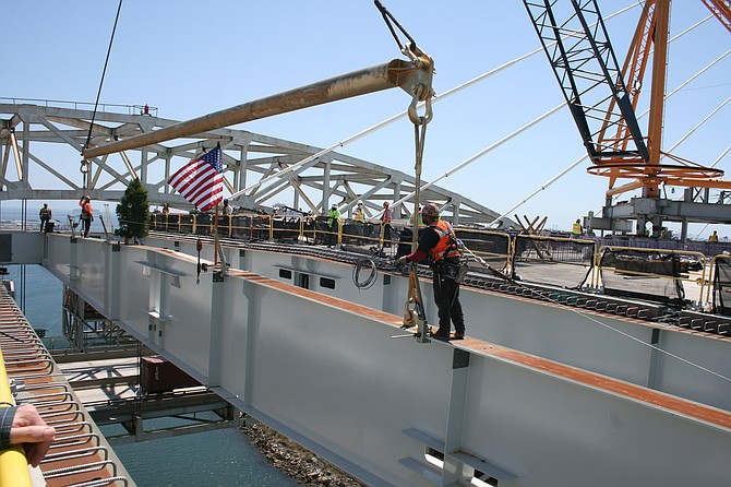 Crews lift the final floor beam into place for the main span of the new Gerald Desmond Bridge.