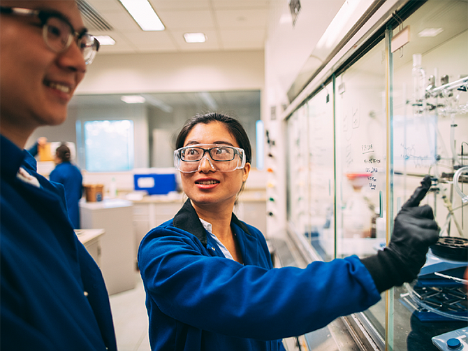 Photo courtesy of Cyclopure. Yuhan Ling, left, and Shan Li discuss particle size equations at Cyclopure, which is commercializing its water purification product.