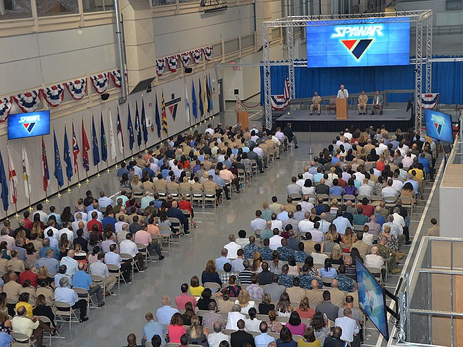 Photo courtesy of U.S. Navy. A 2017 meeting at NAVWAR, then called SPAWAR, shows the cavernous space of the command's buildings. NAVWAR makes its home in a repurposed 1940s aircraft factory.