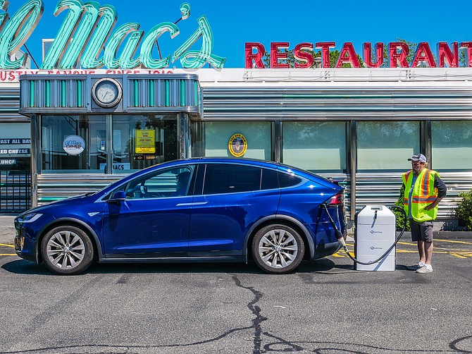 Local roadside assistance powers up a Tesla Model X at Al Mac's Diner in Fall River, Mass.