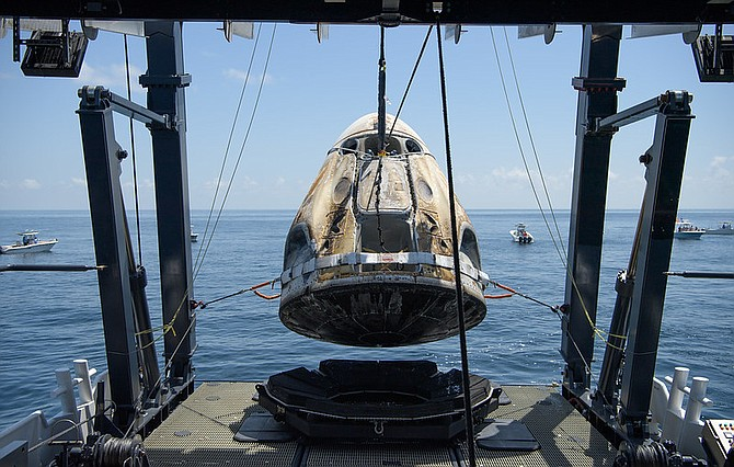 The SpaceX Crew Dragon Endeavour spacecraft is lifted onto the SpaceX GO Navigator recovery ship shortly after it landed with NASA astronauts Robert Behnken and Douglas Hurley onboard in the Gulf of Mexico off the coast of Pensacola, Florida, Aug. 2, 2020.