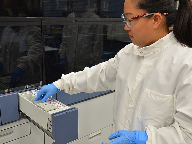 Photo courtesy of Hologic Inc. Yecong Li, Ph.D., an R&D scientist at Hologic, loads a COVID-19 test on a Panther machine.