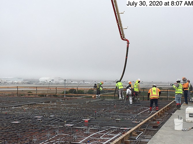 Workers complete the last concrete pour at at an LAX parking facility.