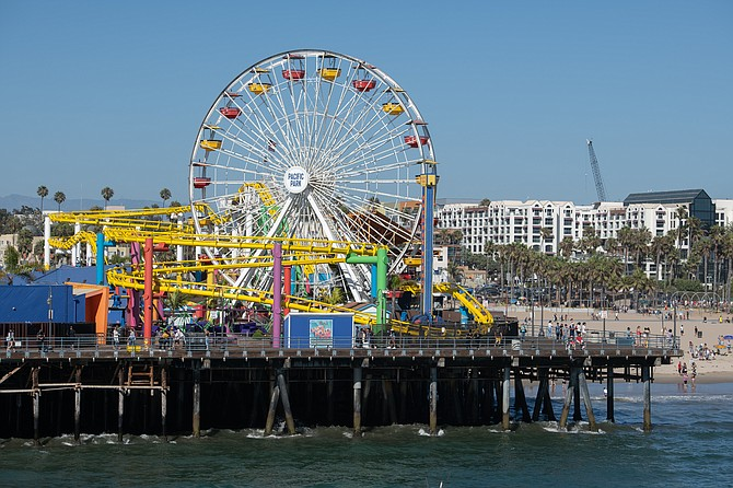 The coronavirus outbreak shuttered the Santa Monica Pier for more than two months. When it was allowed to reopen, visitors returned in smaller numbers and found that the offerings were limited. Rides at Pacific Park (bottom) remain closed.