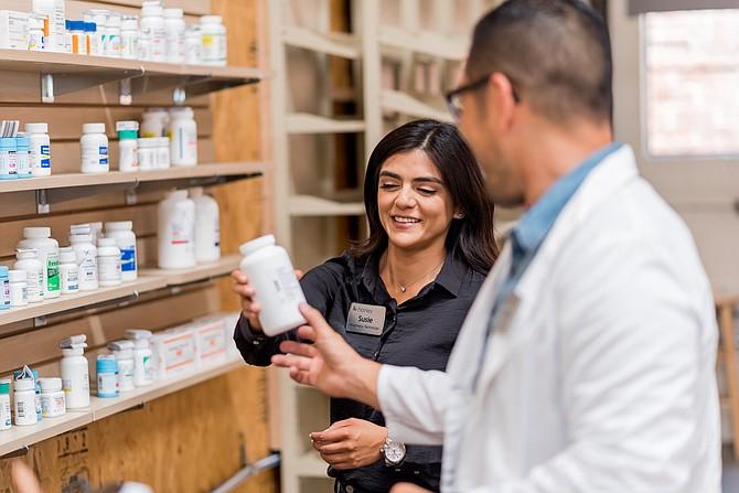 Susie Morales of Honeybee Health, which has seen a surge in orders, speaks with pharmacist James Kim.