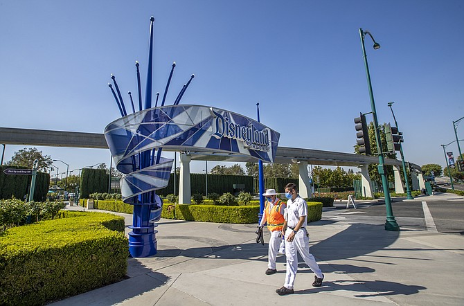 Cast members walk past Disneyland Park's entrance a day after the company announced thousands of layoffs.