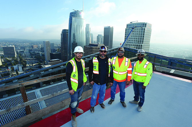 ACCO sheet metal workers stand on the roof of the Metropolis downtown.