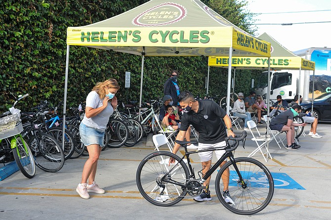 Mike Davis, store manager Helen's Cycles, helping a customer near the waiting area.