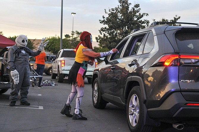 """Jack"" and ""Sally"" hand out candy at The Shops at Montebello's drive-thru Halloween event."