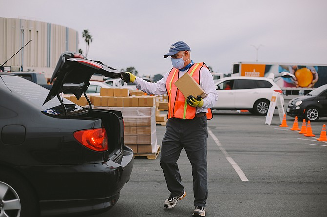 A Feeding San Diego volunteer helps a client stock their pantry during a drive through food distribution event at Pechanga Arena. Photo by Carly Matsumoto, courtesy of Feeding San Diego.